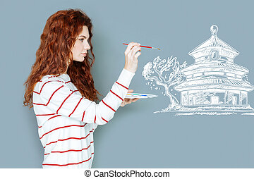 Attentive artist holding a brush and painting a house