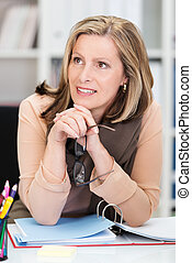 Attentive attractive businesswoman sitting at her desk with...