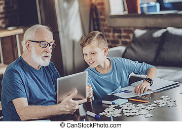 Attentive boy looking at tablet of his granddad - Look here....