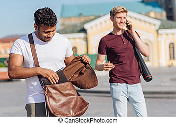 Attentive brunette man putting his tablet into bag