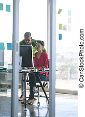 Attentive business people working at desk in creative office