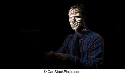 Attentive businessman after work sitting alone in a dark room enjoying himself by playing a computer game while the screen reflects on his face