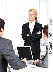 Attentive businesswoman - A businesswoman standing at a...