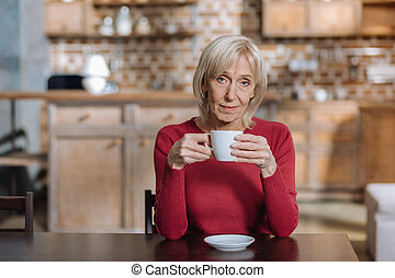 Attentive calm woman drinking tea at home