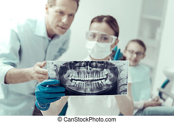 Attentive dentist showing the X-ray to a patients father