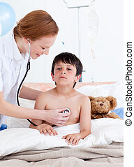 Attentive doctor examining a little boy