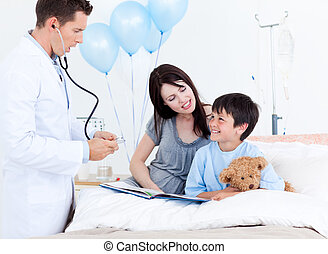 Attentive doctor talking with a little boy and his mother at...
