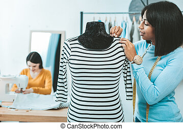 Attentive fashion designer making dress