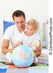 Attentive father and his child holding a terretrial globe