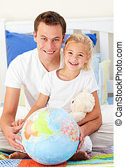 Attentive father and his daugther looking at a terrestrial globe sitting on bed