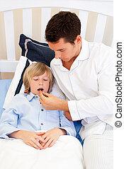 Attentive father checking his son\'s temperature