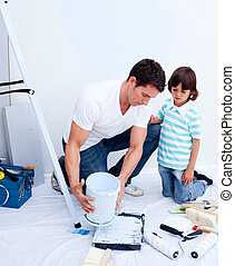 Attentive father decorating a new flat with his son