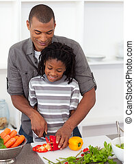 Attentive father helping his son cut vegetables in the...