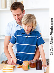 Attentive father helping his son prepare the breakfast