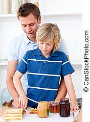 Attentive father helping his son prepare the breakfast