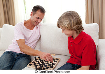 Attentive father playing chess with his son