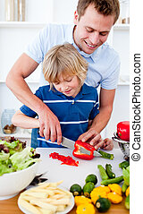 Attentive father preparing dinner with his son in the kitchen