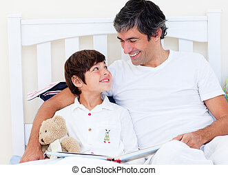 Attentive father reading with his son sitting on a bed