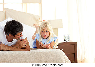Attentive father talking with his daughter lying on bed