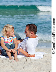 Attentive father talking with his daughter lying on the sand