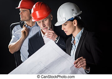 Attentive female and male architect in helmet holding blueprint on black