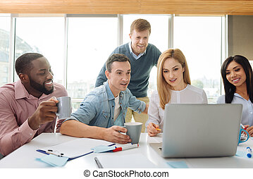 Attentive female person explaining news to her colleagues -...