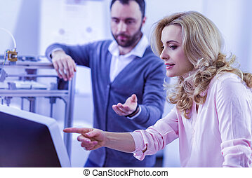 Attentive female person pointing at screen of computer