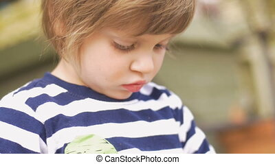 Attentive focused concentrating young healthy little girl outside in slow motion