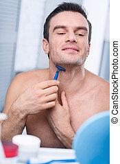 Attentive focused man shaving his neck