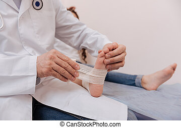 Attentive gentle doctor doing a dressing