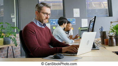Attentive male executive using laptop in office 4k