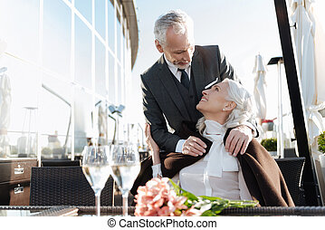 Attentive male person embracing his woman