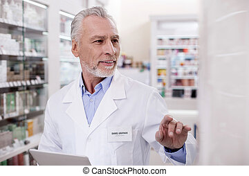 Attentive male pharmacist checking online catalog