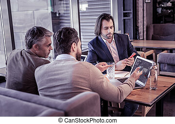 Attentive males staring at screen of laptop
