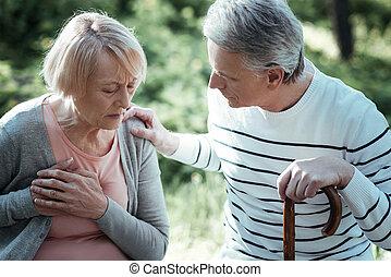 Attentive man helping his sick woman