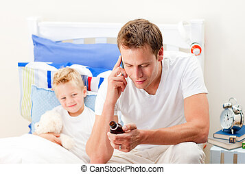 Attentive man looking after his sick son lying in his bed