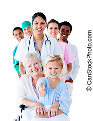 Attentive medical team taking care of a senior woman and her granddaughter against a white background