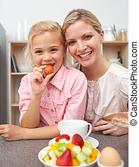 Attentive mother eating fruit with her daughter