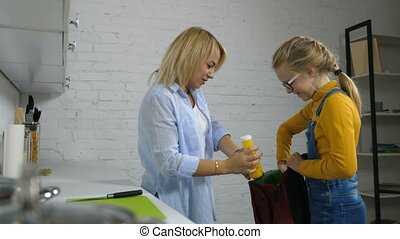 Attentive mother giving school lunch to her daughter