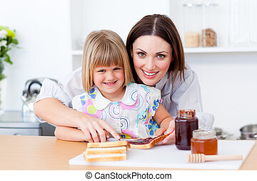 Attentive mother helping her daughter prepare the breakfast
