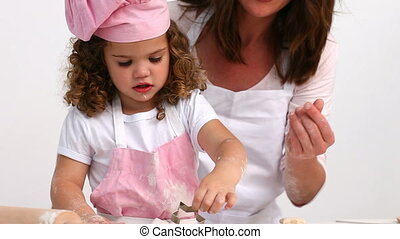 Attentive mother helping her daughter to bake