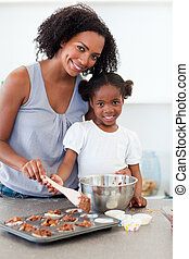 Attentive mother helping her girl cooking biscuits in the...