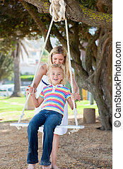 Attentive mother pushing her child on a swing in a park