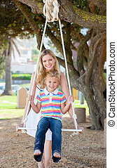 Attentive mother pushing her child on a swing