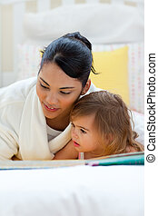 Attentive mother reading with her daughter lying on a bed