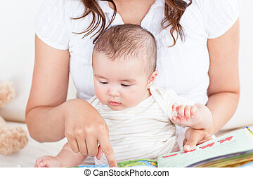 Attentive mother showing images in a book to her cute little son at home