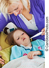 Attentive mother takes her daughter\'s temperature