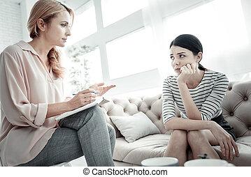 Attentive pretty woman sitting and listening. - Listen...