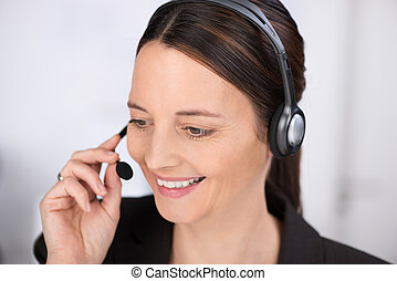 Attentive receptionist talking on a headset smiling as she...