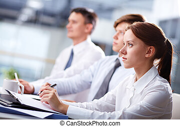 Attentive - Row of business people attending a seminar and...